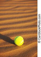 tennis ball in desert sand