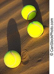 tennis balls in desert sand