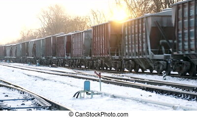 cargo train move on rail road at winter sunset