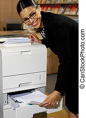 Pretty young businesswoman using Xerox machine at the office...