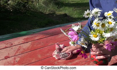 vase with flowers - farmer cleaning wooden table in yard and...
