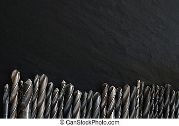 Old drill bits over stone background