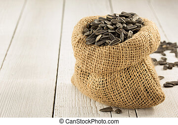 sunflower seeds in bag on wooden background