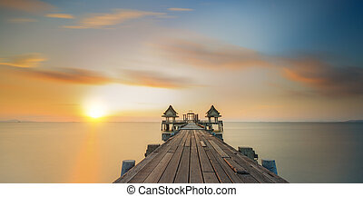 Wooded bridge connect oil temple with the beach along sunset...