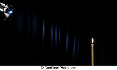 A wax candle burning on a black background On the background...