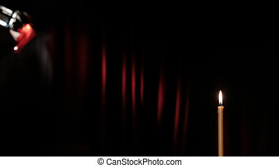 A wax candle burning on a black background Against a...