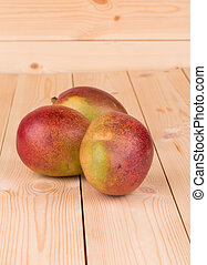 ripe mangoes - isolated ripe mangoes on the wooden table