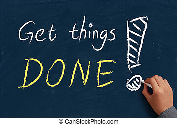 Get things done on blue chalkboard with the hand of...