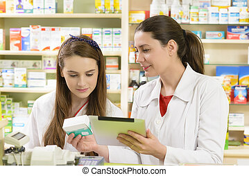 Drugstore - Two young female pharmacist in a drugstore...