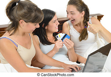 Online Shopping - Three young women having fun and making...