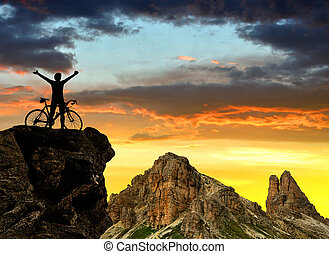 Cyclist on bike at sunset In the background Dolomite Alps