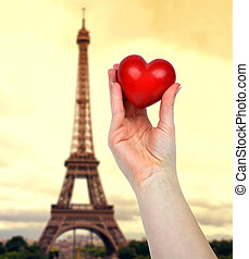 Hand holding heart In the background Eiffel tower