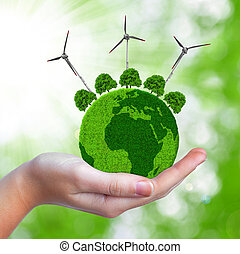 Green planet with trees and wind turbines in hand