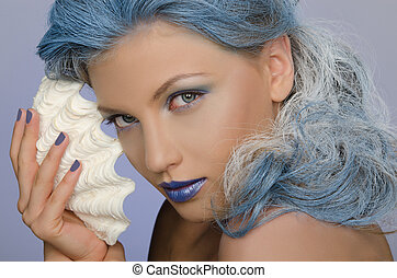 charming woman with blue hair and seashells looking at...