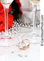 Two golden wedding rings, champagne glasses, red roses