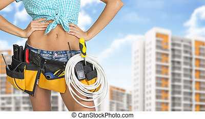 Woman in tool belt. Hands on hip. Buildings and sky as backdrop