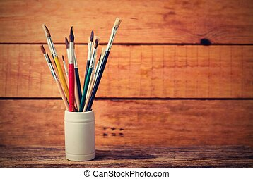 Vintage retro photo of jar with paintbrushes