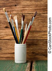 White jar with paintbrushes on green board