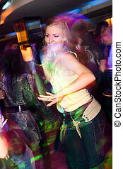 Young girl dancing in the nightclub - Young pretty blond...