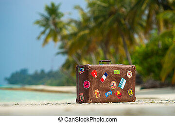 Travel vintage suitcase is alone on a beach - Travel vintage...