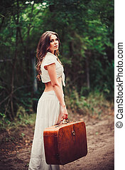 Beautiful young sad woman with suitcase in hand standing on...