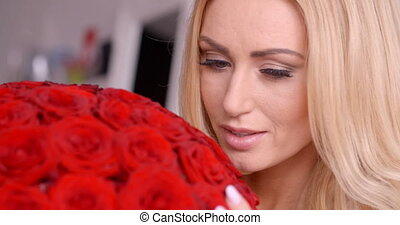 Seductive Blond Woman Behind Red Rose Bouquet - Close up...