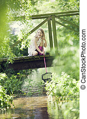Young Girl Catching Fish With Net From Wooden Bridge