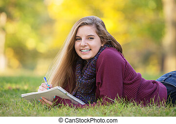 Female Teen on Ground Studying - Female teen with braces...