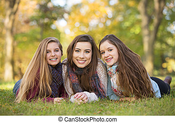 Trio of Friends - Three happy Caucasian teen girls sitting...