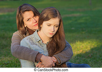 Mother with Sad Daughter - Concerned European mother holding...