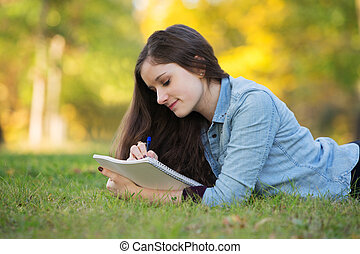 Teen Doing Homework Outside - Grinning young woman writing...