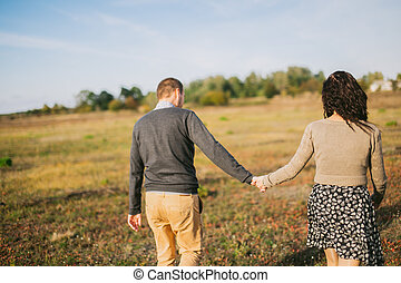 Young couple walks at sunset holding hands - Image of a...