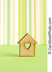 Wooden house with hole in the form of heart on green striped...