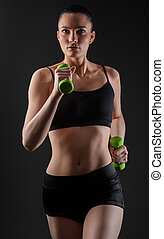Fitness woman working out with green dumbbell. Running model