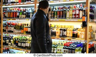 man choosing products in alcoholic during weekly shopping at...