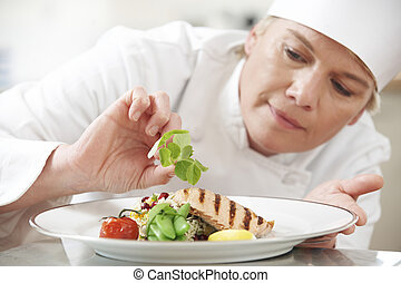 Chef Adding Garnish To Meal In Restaurant Kitchen