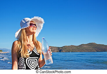Young blond woman with bottle of water - Young smiling blond...
