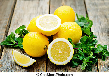lemons and mint on a dark wood background. tinting....