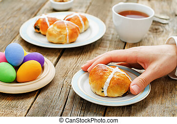 Easter Breakfast. Man holding the bun with a cross. tinting....