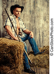 country style - Sexy cowboy on a haystack. Western style.