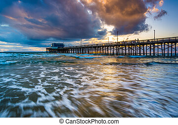Waves in the Pacific Ocean and the Newport Pier at sunset,...