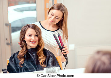 Beautiful woman in hair salon - Going for big curls. Mirror...
