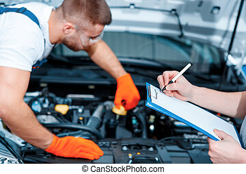 Car mechanics at the service station - Running diagnostics....
