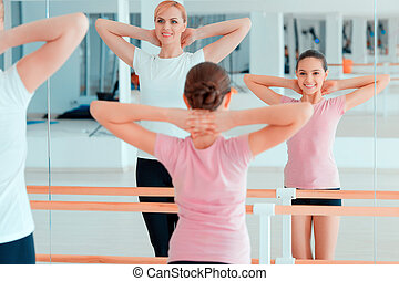 Mother and teenage girl at dancing club - Stretching is a...