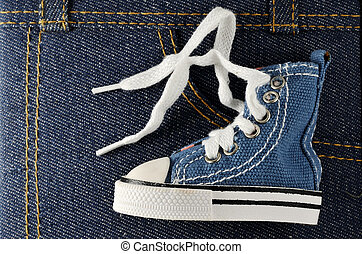 tiny blue shoe on denim background