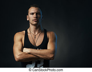 man on black background with his arms crossed