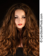 Beautiful mysterious young brunette woman with amazing curly...