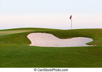 Sand bunker in front of golf green and flag - Red flag of...