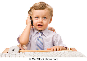 Boy with cell phone - Young boy sitting at the office desk...