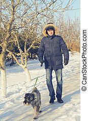 Man walking his dog on a snowy path
